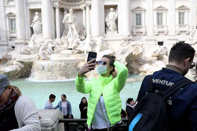 Woman in front of fountain taking selfie